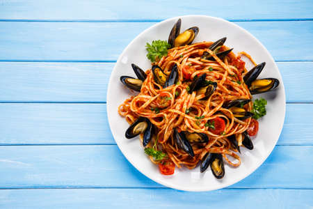 black dish: Cooked mussels and pasta