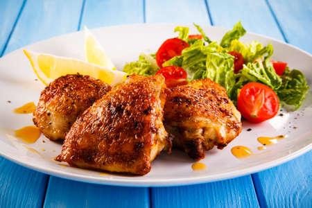 pollo a la brasa: muslos de pollo y verduras a la parrilla Foto de archivo