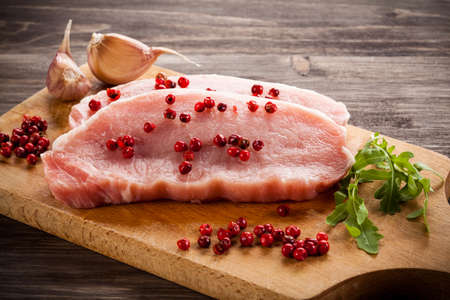poultry: Raw pork chops on cutting board and vegetables