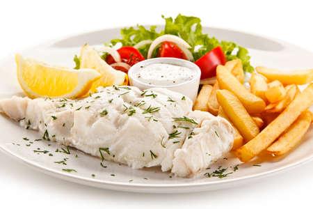 Vis schaaltje - gekookte vis filet, gebakken aardappelen en groenten Stockfoto