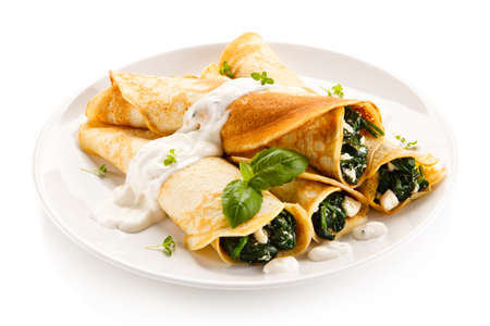 crepas: Crepes with spinach and feta cheese on white background