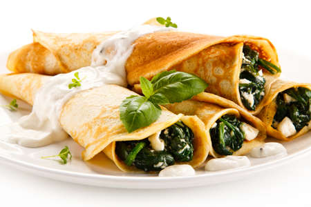 white cheese: Crepes with spinach and feta cheese on white background