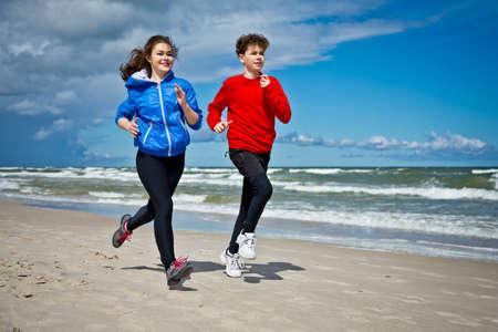 personas corriendo: Gente joven que funciona en la playa Foto de archivo