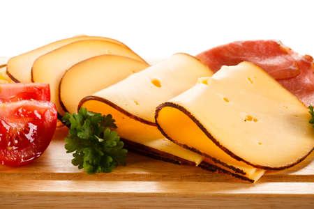 jamon y queso: Queso con jamón ahumado en la tabla de cortar
