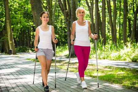 Las mujeres nordic walking en el parque