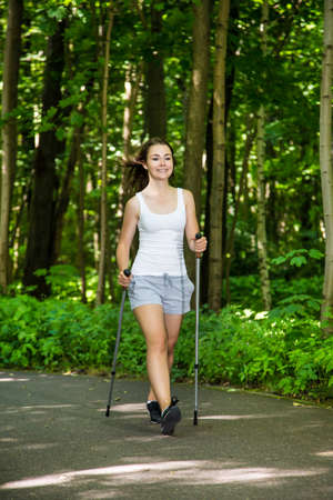 enjoymant: Young woman nordic walking in the park
