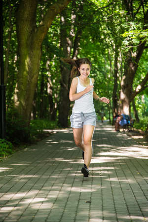 enjoymant: Young woman running in the park Stock Photo
