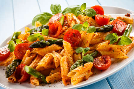 Pasta with asparagus and tomatoes Stock Photo