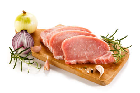 red onions: Raw pork chops on cutting board and vegetables