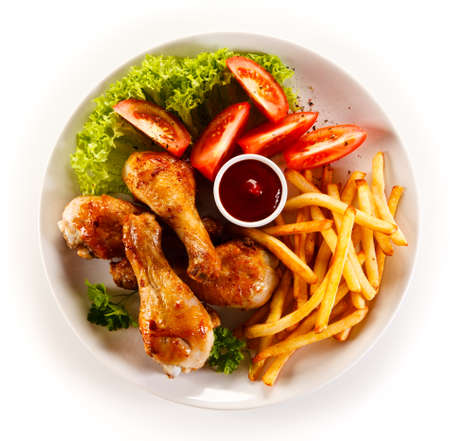 pollo frito: Roasted drumsticks with french fries Foto de archivo