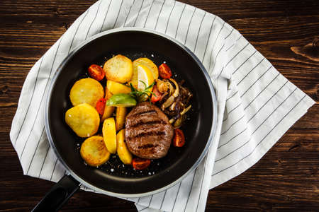 plato de ensalada: Roasted steak with potatoes served on frying pan