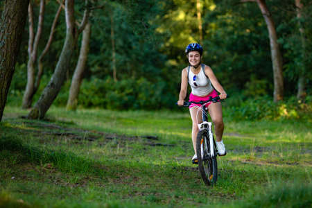 Young woman cycling outdoors Stock Photo