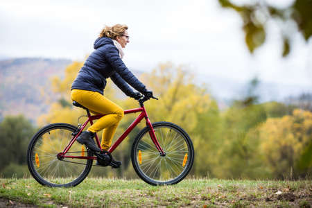 Woman cycling in park Stock Photo
