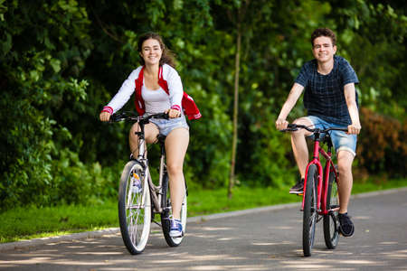 19's: Boy and girl biking in the city park