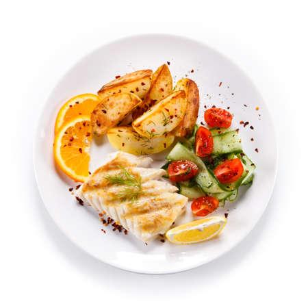 Fried fish with potatoes Фото со стока