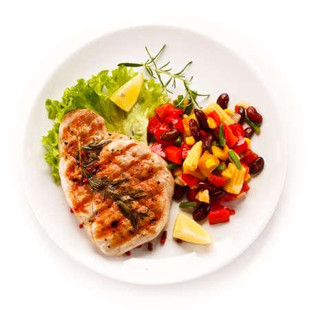 Filete asado y verduras sobre fondo blanco