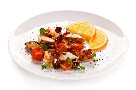 Grilled chicken with vegetables on a white background