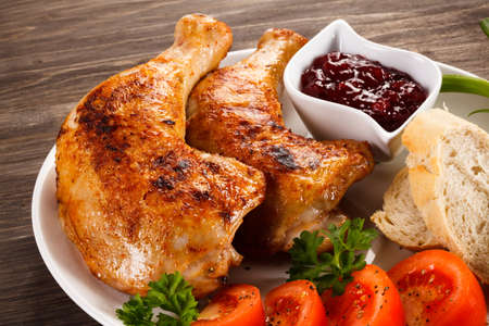 Grilled chicken legs and vegetables on wooden background