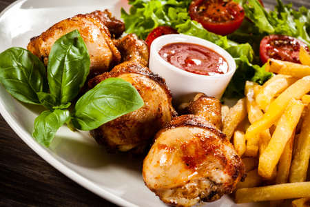 Drumsticks with french fries and vegetables