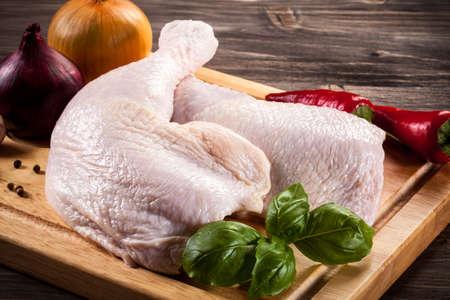 Raw chicken legs on cutting board