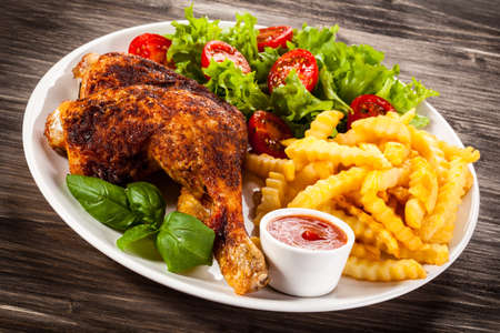 drumsticks: Grilled chicken leg with chips and vegetables Stock Photo