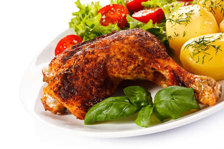 Barbecued chicken leg with boiled potatoes and vegetables Stock Photo