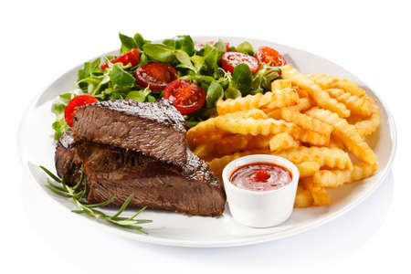 Grilled steak, French fries and vegetables on a white background 스톡 콘텐츠