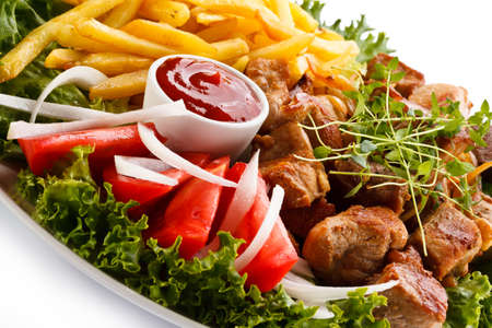Kebab - grilled meat with French fries and vegetables Stock Photo