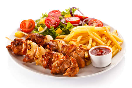 Kebabs - grilled meat and vegetables on white background
