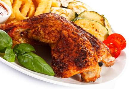 drumsticks: Grilled chicken legs, chips and vegetables Stock Photo