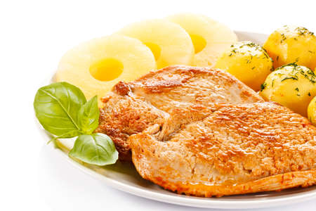 Fried chicken fillets, boiled potatoes and pineapples Stock Photo