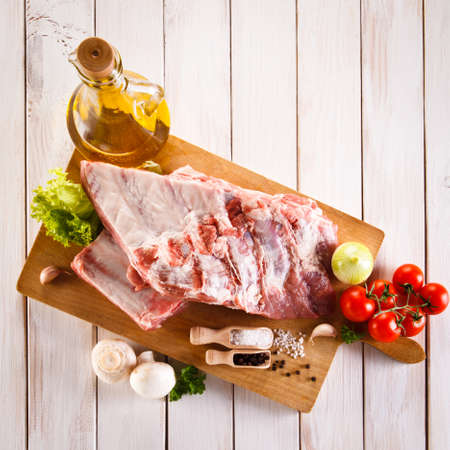 raw: Raw pork ribs on cutting board and vegetables Stock Photo