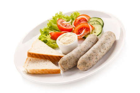 Breakfast - boiled white sausages, toasts and vegetables Stock Photo