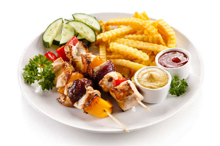 Grilled meat, French fries and vegetables Stock Photo