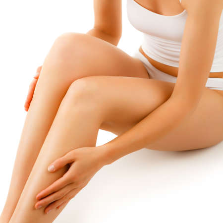 Woman massaging legs sitting on a white background