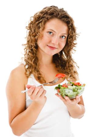 白で隔離の野菜サラダを食べる若い女性