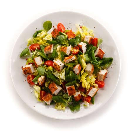 白い背景の上に野菜と鶏のグリル