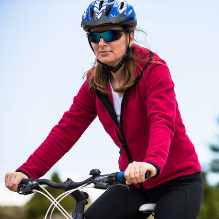 mtb: Middle-aged woman riding bicycle Stock Photo