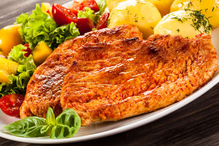 Fried chicken fillets, boiled potatoes and vegetable salad Stock Photo
