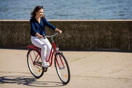 Urban biking - young woman riding bike photo