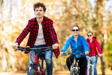 Healthy lifestyle - people riding bicycles in city park photo