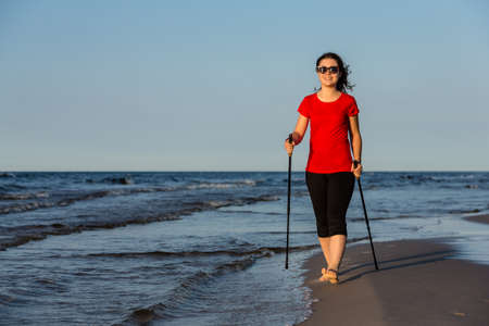Nordic walking - woman working out on the beach photo