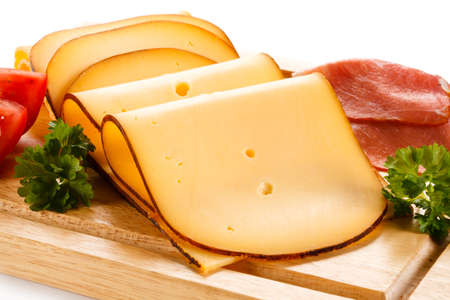 Cheese on cutting board on white background Stock Photo