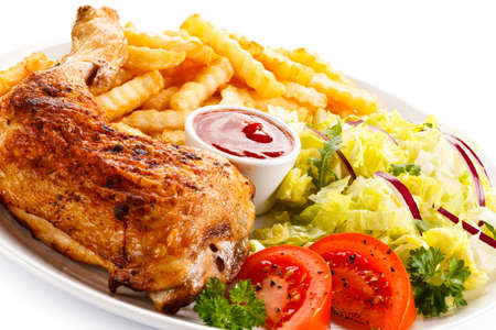 Grilled chicken leg with french fries and vegetables Stock Photo