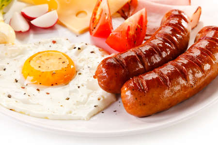 Breakfast - fried egg and sausages, cheese, ham and vegetables Stock Photo