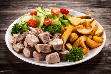 Grilled meat with baked potatoes and vegetables Stock Photo