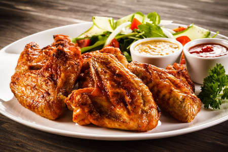 Grilled chicken wings and vegetable salad Stock Photo