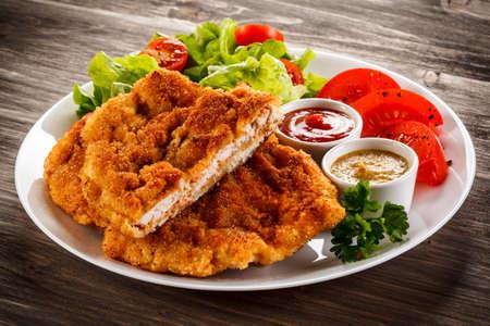 Chuletas de cerdo frito y ensalada de verduras Foto de archivo - 84055705