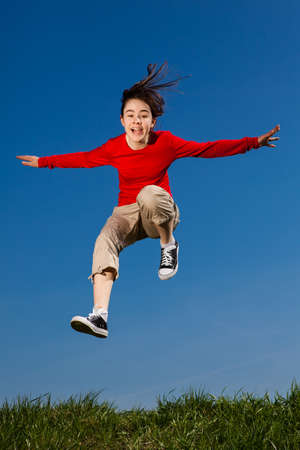 Teenage girl jumping, running outdoor against blue sky photo