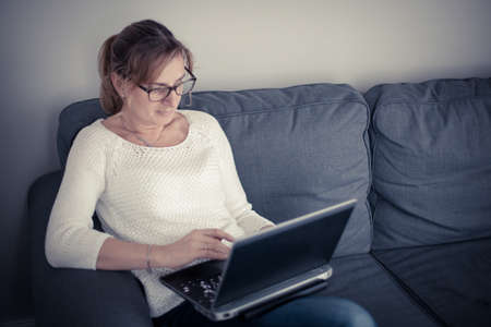 couch: Middle-aged woman using laptop at home Stock Photo
